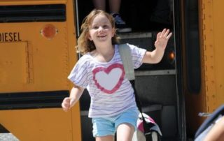 girl smiling by school bus
