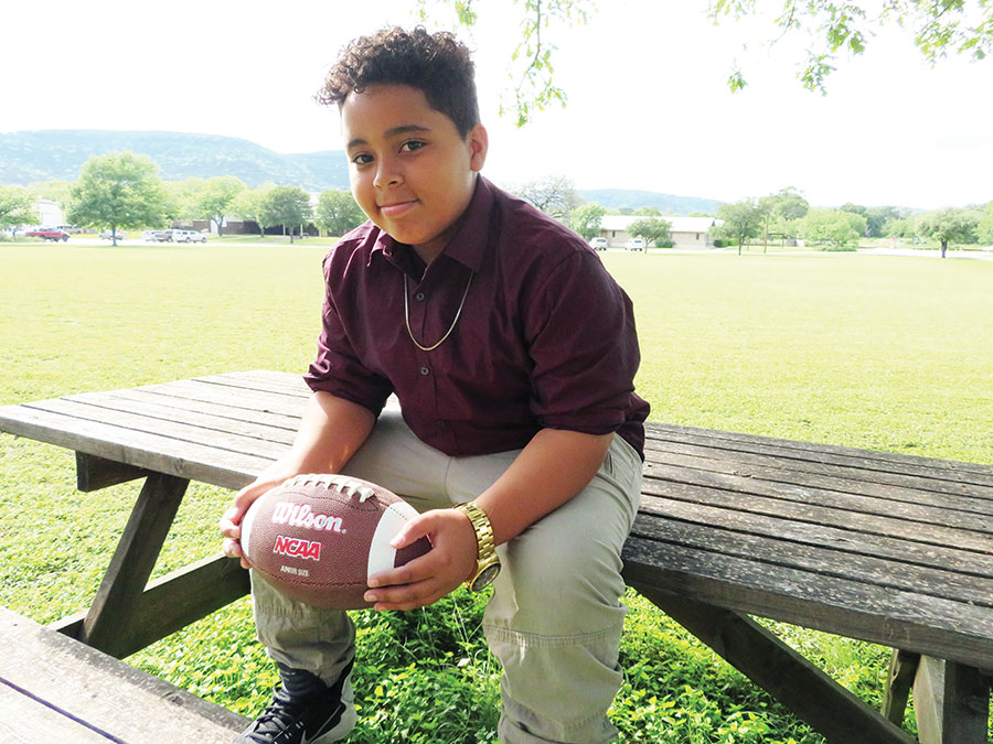 boy sitting on a picnic bench with football